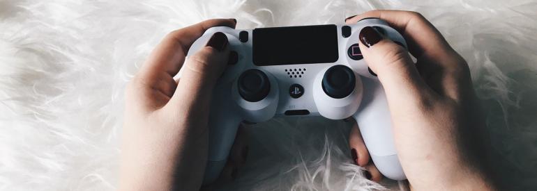 Weibliche Hände mit lackierten Fingernägeln halten einen PlayStation-Controller.